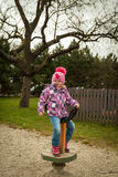 Small girl having fun on the children's attractions Royalty Free Stock Photo