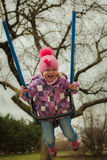 Small girl having fun on the children's attractions. In the park Stock Image