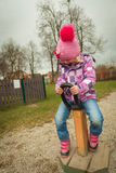 Small girl having fun on the children's attractions. In the park Royalty Free Stock Photography