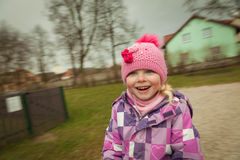 Small girl having fun on the children's attractions. In the park Stock Photography