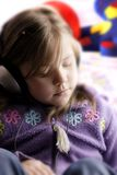 Small Girl and headphones. Small girl wearing headphones and listening to the music Royalty Free Stock Image