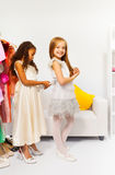 Small girl helps her friend by fitting the dress Stock Images