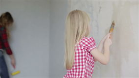 A small girl and her mother hanging new wallpaper. stock footage