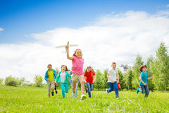 Small girl holding airplane toy and kids behind royalty free stock photography