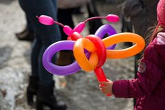A freelance clown creating balloon animals and different shapes at outdoor festival in city center. stock photos