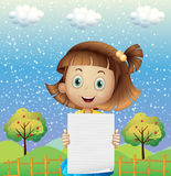 A small girl holding an empty paper near the fence Stock Images