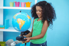 Small girl holding a globe of the world. In her room royalty free stock photo