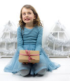 Small girl holding present with christmas decorations  behind Royalty Free Stock Images