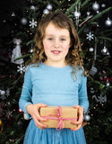 Small girl holding present with christmas tree behind Stock Photo