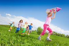 Small girl holding rocket carton toy and kids run Stock Photos