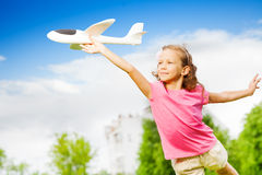 Small girl holds airplane toy with straight arm Stock Photo