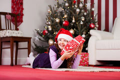 Small girl hugging her Christmas present Royalty Free Stock Image