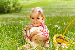 Small girl hugging rabbit in field. Small girl cuddling rabbit in green field with basket with Eastern eggs nearby Royalty Free Stock Photos