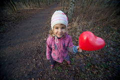 Small girl with inflatable red heart Stock Photos