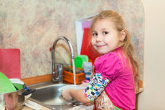 Small girl in the kitchen washing dishes Royalty Free Stock Photography