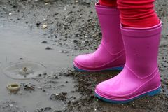 Small girl legs in pink rubber boots and drops in puddle of mud. Small, two years old girl legs in pink rubber boots standing next to puddle of mud with two stock photo