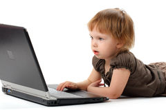 Small girl lieing and learning at notebook Royalty Free Stock Photo