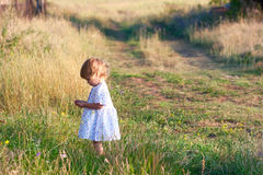 Small girl in the light dress is taking a walk Stock Image