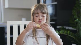 Small girl with long hair in white dress makes a mustaches from the raw dough when preparing a cookies for bake. Child. Making cookies from raw dough in the stock video