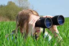 Small girl looking through binoculars Stock Images