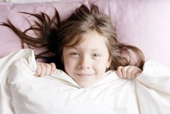 Small girl looking at camera. Small and smiling girl waking up on a sunny morning Royalty Free Stock Photos