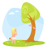 Small girl looking curiously at a cat on a tree Royalty Free Stock Photo