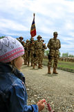 Small girl looking for her dad. Small girl attending a military parade in the honor of one thousand soldiers that are about to live in Afghanistan Stock Image