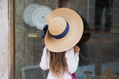 Small girl looking at shop window. Girl in large straw hat and white dress is sitting on her knees and looking through the shop window Stock Photo