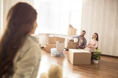 Small girl is looking to her parents. Young man and woman are unpacking boxes for their new home and looking to their. Small girl is looking to her parents Royalty Free Stock Photos
