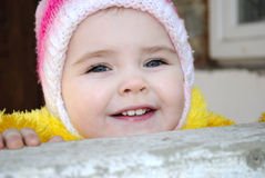 Small girl looks out behind a parapet Royalty Free Stock Images