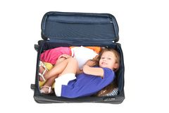 Small girl lying in black suitcase. Royalty Free Stock Photography