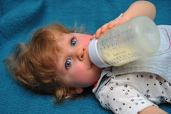 Small girl lying on blue sofa and drink milk from flask Stock Image