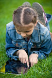 Small girl lying on grass and pointing at touchscreen Royalty Free Stock Photo