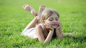 Small girl lying on green grass in park. Glad small girl in elementary school age lying on green grass in park stock video footage