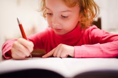 Small girl making her first homework. Focused stock images