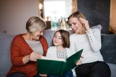 A small girl with mother and grandmother at home. A small girl with her mother and grandmother at home. Family and generations concept Royalty Free Stock Photos