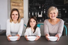 A small girl with mother and grandmother at home. A small girl with her mother and grandmother at home, holding bowls. Family and generations concept Royalty Free Stock Photos