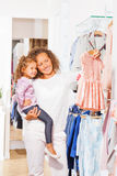 Small girl with mother holding the chosen dress Stock Photos