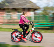 Small girl in motion riding down the street Royalty Free Stock Photos