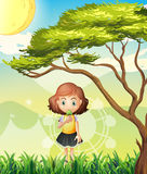 A small girl near the big tree Stock Photography