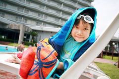 Small girl near the pool. Covering a beach towel and staring at Stock Photo