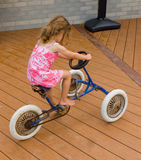 A small girl on an old tricycle Royalty Free Stock Photography