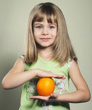 Small girl with orange Royalty Free Stock Images