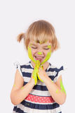 Small girl with paint on her cheek and nose Royalty Free Stock Photos