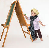 Small girl painting. Small girl has completed painting at a wooden easel Stock Image