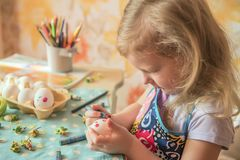 A small  girl paints Easter eggs. A small sweet blonde girl paints Easter eggs. Preparing for the holiday of Easter Royalty Free Stock Photos