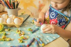 A small girl paints Easter eggs. A small sweet blonde girl paints Easter eggs. Preparing for the holiday of Easter.n Royalty Free Stock Image