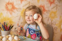 A small girl paints Easter eggs. A small sweet blonde girl paints Easter eggs. Preparing for the holiday of Easter.n Stock Image