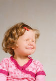 Small girl in a ping dress. Small blinking beautiful girl in a pink dress Royalty Free Stock Photo
