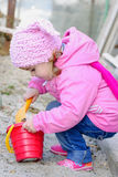 The small girl in pink clothes plays sand Stock Photo
